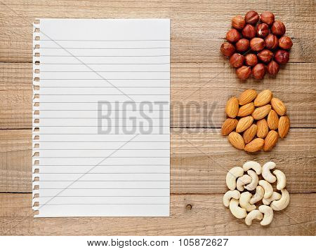 Filberts, Almonds, Cashew Nuts And Paper For Recipe On Wooden Background