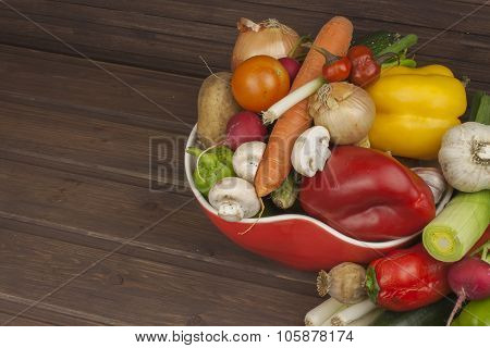 Vegetables in red desk space, space for text. Various types of vegetables on an old wooden table.