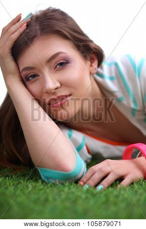 Beautiful young woman lying on green grass