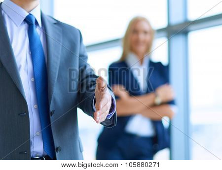Young business man ready to handshake standing in office