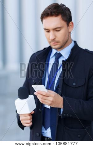 Handsome newsgatherer is busy working on the phone.