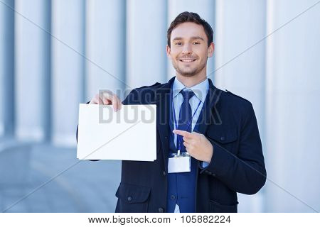 Smiling reporter points at sheet of paper.