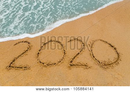 2020 Inscription Written On Sandy Beach With Wave Approaching