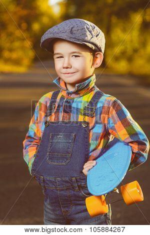 Smiling boy holding color plastic penny board skateboard outdoor