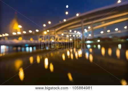 Abstract blurred bokeh light, water reflection of highway with suspension bridge
