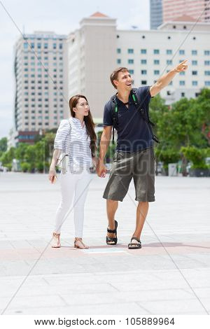 Couple asian girl and caucasian man tourist smile point finger sightseeing