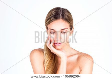 Spa & Beauty. Beautiful woman touching her face by hand and looking down