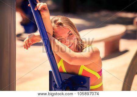 Portrait Of Blonde Girl In Bikini Leans On Simulator Smiles