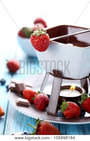 Chocolate Fondue With Fresh Berries On A Blue Wooden Table