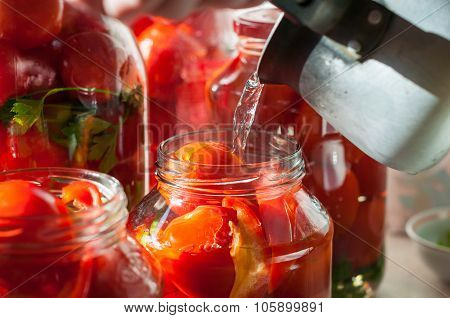 Canning process of tomato in mason jar. On background is few jars with tomatoes. Conservation and co