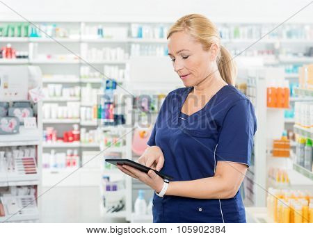 Mature female chemist using digital tablet while standing in pharmacy