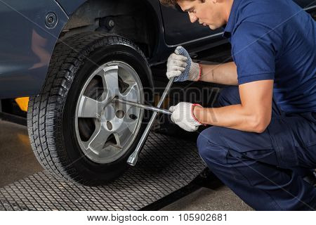 Side view of male mechanic using rim wrench to tighten car tire at garage