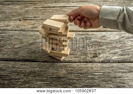 Male Hand Creating Or Building A Tower Of Many Wooden Blocks