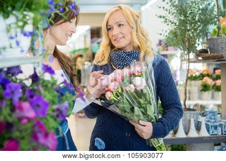 Florist assisting female customer in buying flower bouquet at store