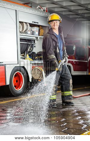 Portrait of confident fireman spraying water on floor during practice at fire station