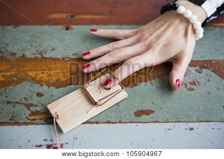 Closeup Of Woman's Finger In Mousetrap