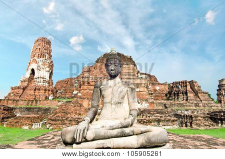 Old buddha in front of ruined pagoda with cloudy white sky in Ayuthaya Thailand