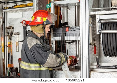 Side view of male firefighter adjusting hose in truck at fire station