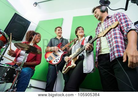Low angle view of happy band members performing in recording studio