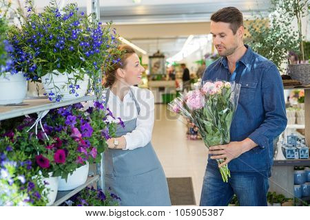 Salesgirl assisting male customer in buying flower bouquet at store