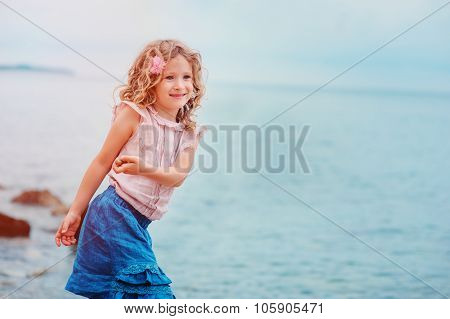 happy child girl relaxing on seaside on summer vacation