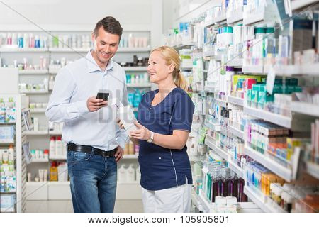 Happy male customer using mobile phone while chemist holding products in pharmacy