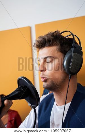 Young male singer performing while holding microphone in recording studio