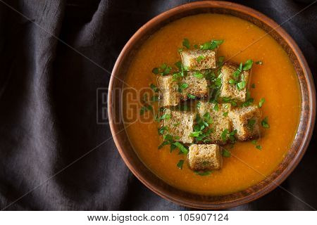 Healthy homemade pumpkin soup traditional recipe with croutons and chopped greens on dark cloth back