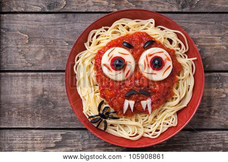 Halloween party decoration food. Spaghetti monster face with big eyeballs, fangs, spider and moustac