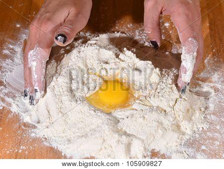 Woman Adding Egg To The Flour