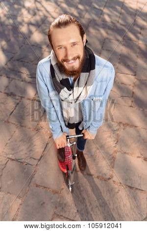 Positive man riding a scooter
