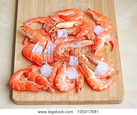 Fresh Red Shrimps With Ice On The Chopping Board