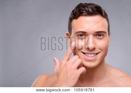 Pleasant man using cream