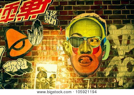 Graffiti With Weird Face On Brick Wall