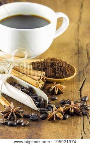 Coffee On The Cup With Coffee Beans And Cinnamon Sticks On Wood Background, Warm Toning, Selective F