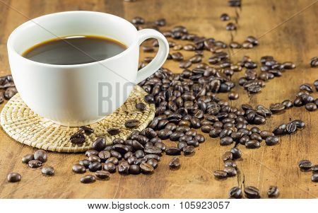 A Cup Of Coffee And Coffee Beans On Wood Background, Warm Toning, Selective Focus