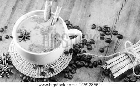 Coffee On The Cup With Coffee Beans And Cinnamon Sticks On Wood Background On Balck And White, Selec