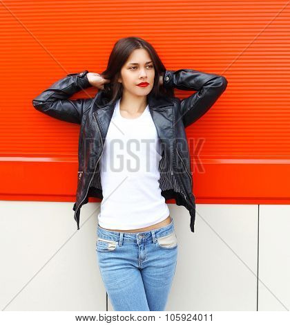 Fashion Pretty Young Woman Wearing A Rock Black Leather Jacket In City Over Red Background
