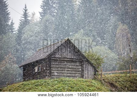 Old country house during heavy snowfall in Carpathians mountains in Ukraine