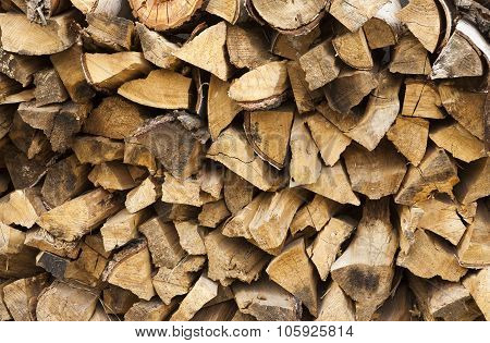 Chopped and stacked pile of pine and birch wood texture background