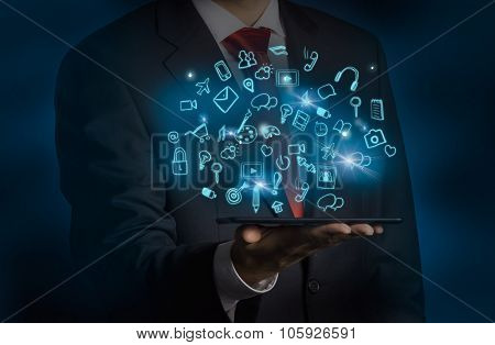 A Man In Formal Suit Is Holding A Tablet With Flying Out Hologram Social Media Icon. Dark Backgroun