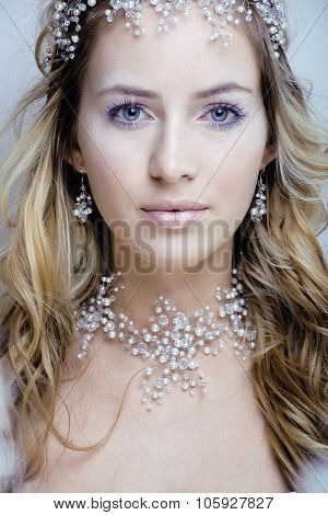 beauty young snow queen in fairy flashes with hair crown on her head close up