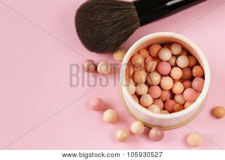 cosmetics rouge balls in the bank on a pink background