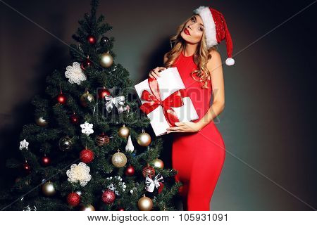 Sexy Blond Santa Holding Present Near The Christmas Tree