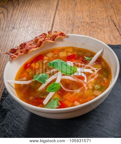 Vegetable soup served with crisp bacon
