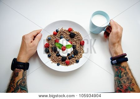 Top View Two Tattooed Hands And Plate With Integral Musli With Berry Mix And Glass Of Milk