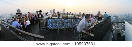 Bangkok, Thailand - April 15,2015: Sunset Over Bangkok Viewed From A Roof Top Bar With Many Tourists