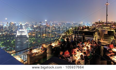 Bangkok, Thailand - April 15,2015: Bangkok By Night Viewed From A Roof Top Bar With Many Tourists En