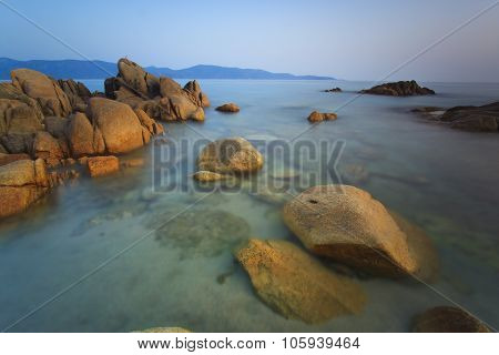 Beach In Corsica With Rocks On Foreground