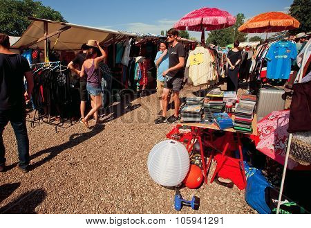 Women And Men Watching Goods In The Piles Of Second Hand
